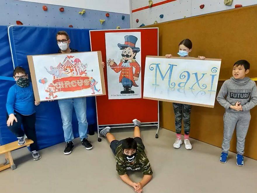 Die Teilnehmer des Zirkusprojekts halten Plakate hoch